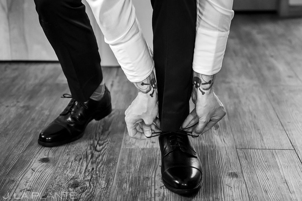groom putting shoes on before wedding