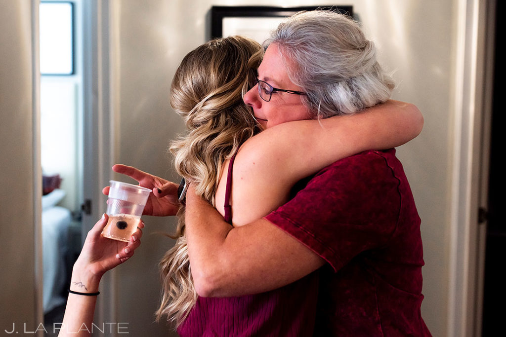 bride hugging her mother while getting ready