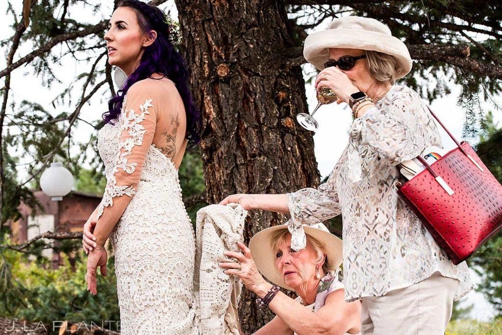 mom and grandma bustling bride's dress during backyard wedding in Boulder