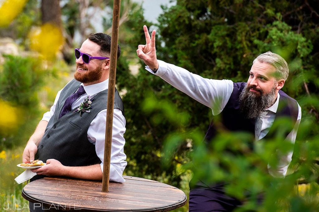 groom giving the best man bunny ears during photos