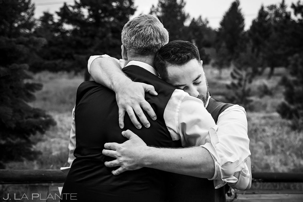 best man hugging the groom during cocktail hour