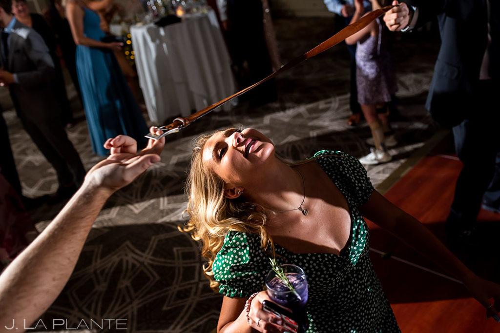 wedding guests doing necktie limbo during wedding reception