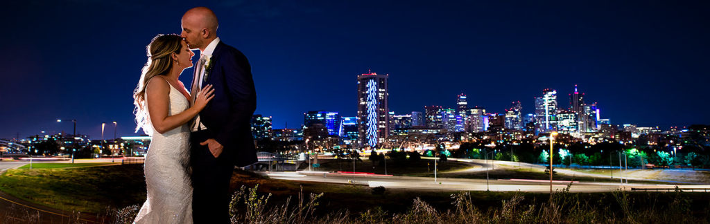 nighttime wedding photo of bride and groom with the Denver skyline in the background