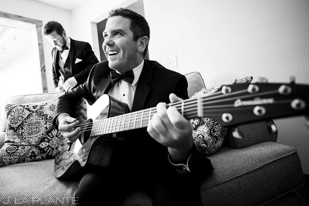 groom playing guitar for groomsmen before wedding