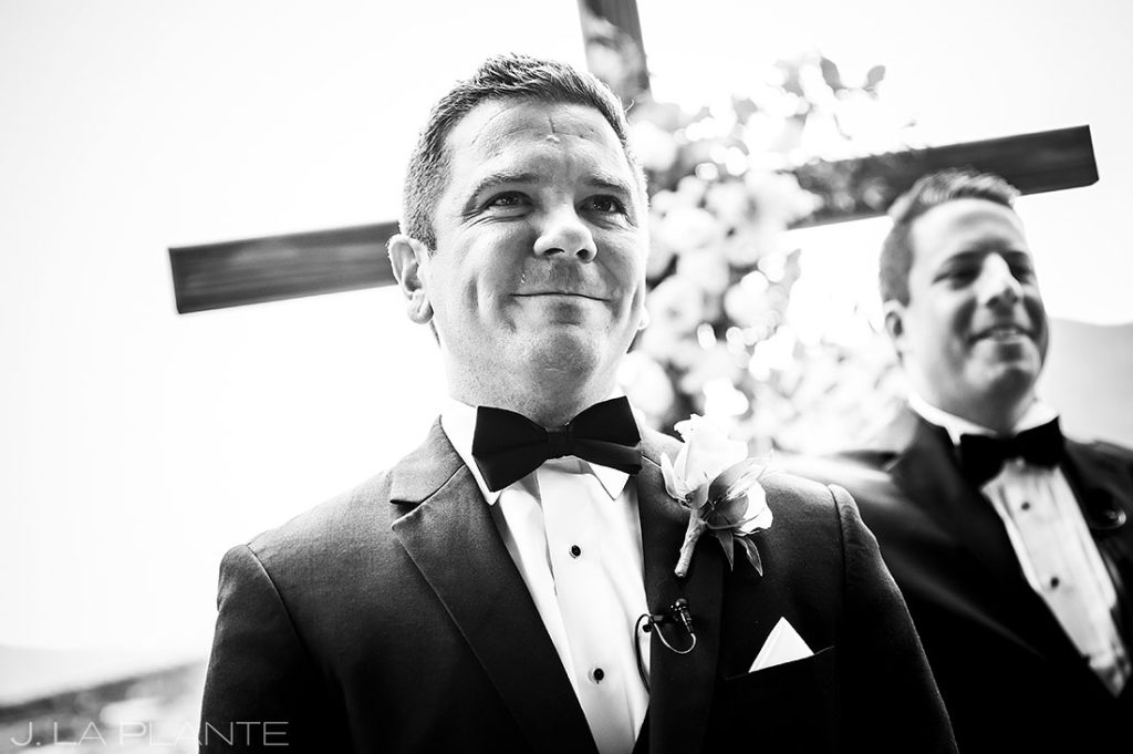 groom crying while watching his bride walk down the aisle
