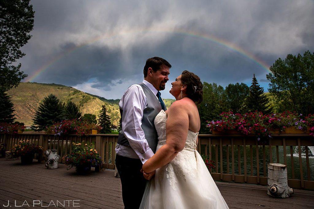 bride and groom under a rainbow