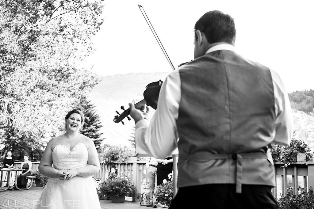 groom surprising the bride with a song on the violin