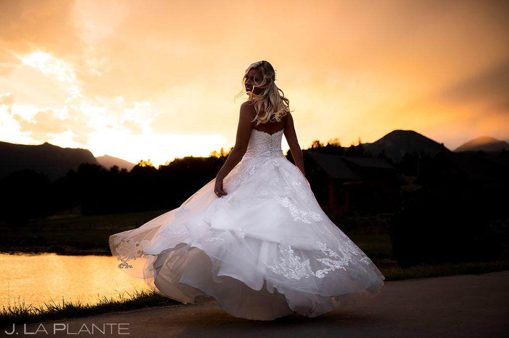 bridal portrait of bride next to mountain lake at sunset