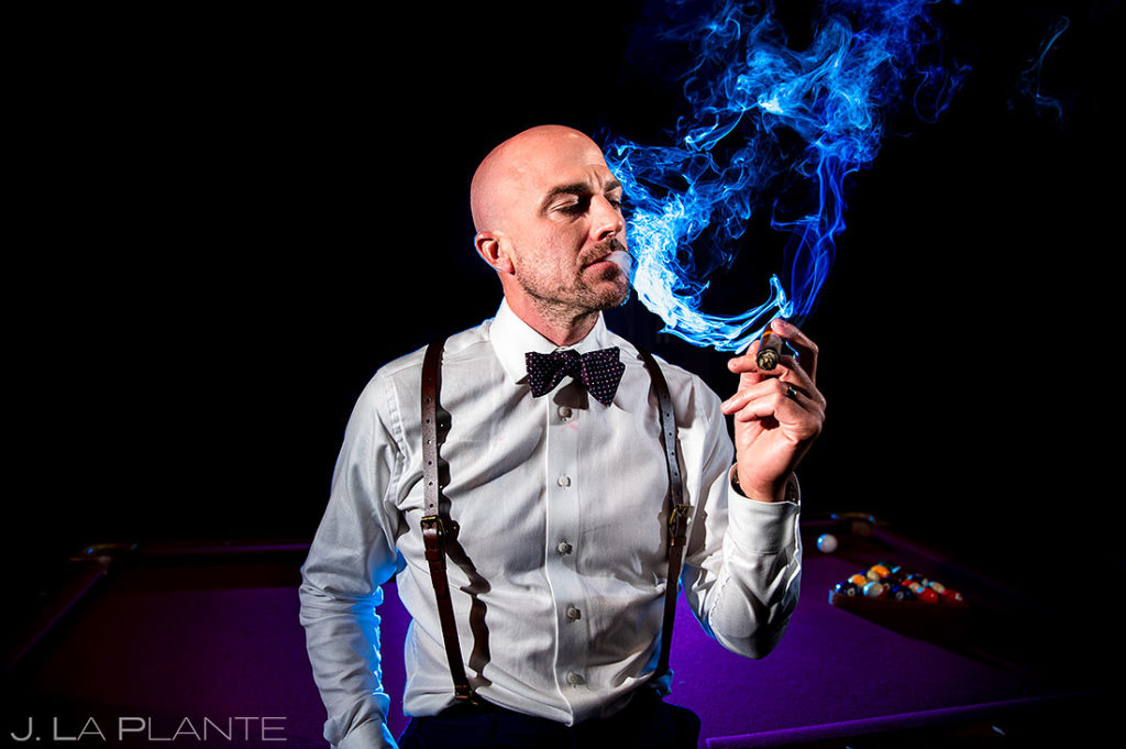 groom smoking cigar at Spruce Mountain Lower Ranch wedding