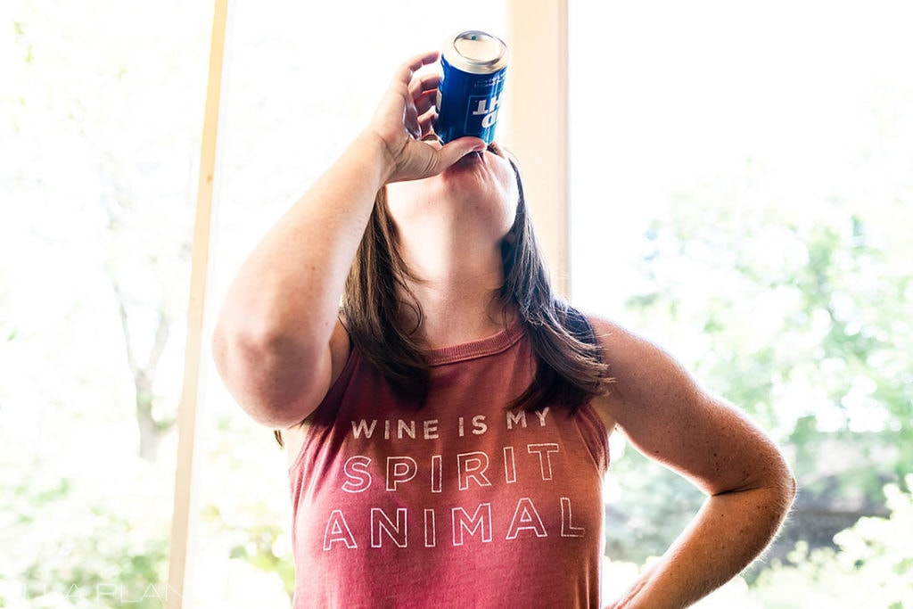 bridesmaid chugging a beer before wedding ceremony