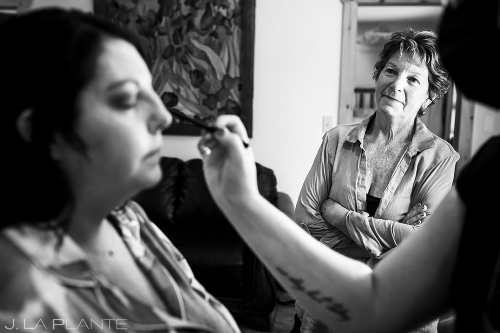 mother of the bride watching bride having makeup done