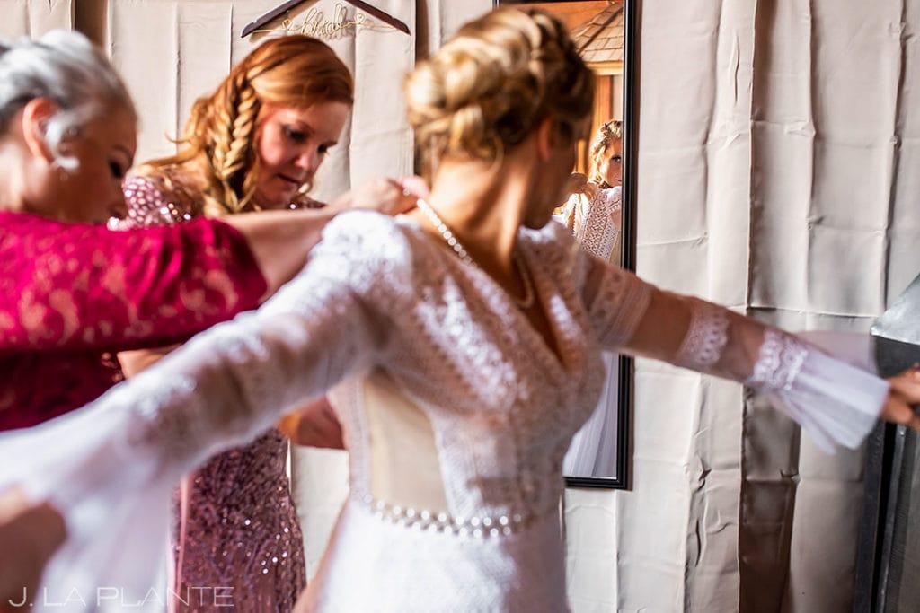 bride getting into dress before Montana destination wedding