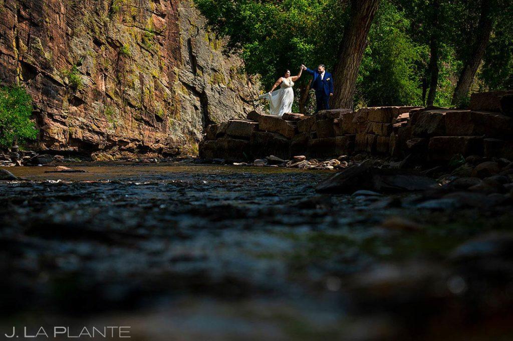 bride and groom dancing by riverside