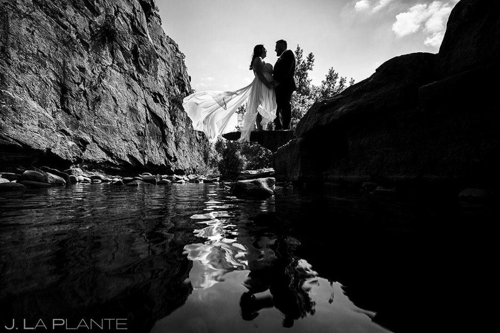 silhouettes of bride and groom standing by river
