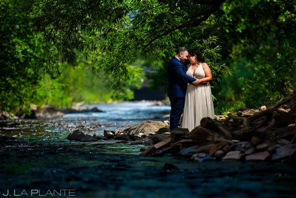 bride and groom by the river at summer wedding at Planet Bluegrass