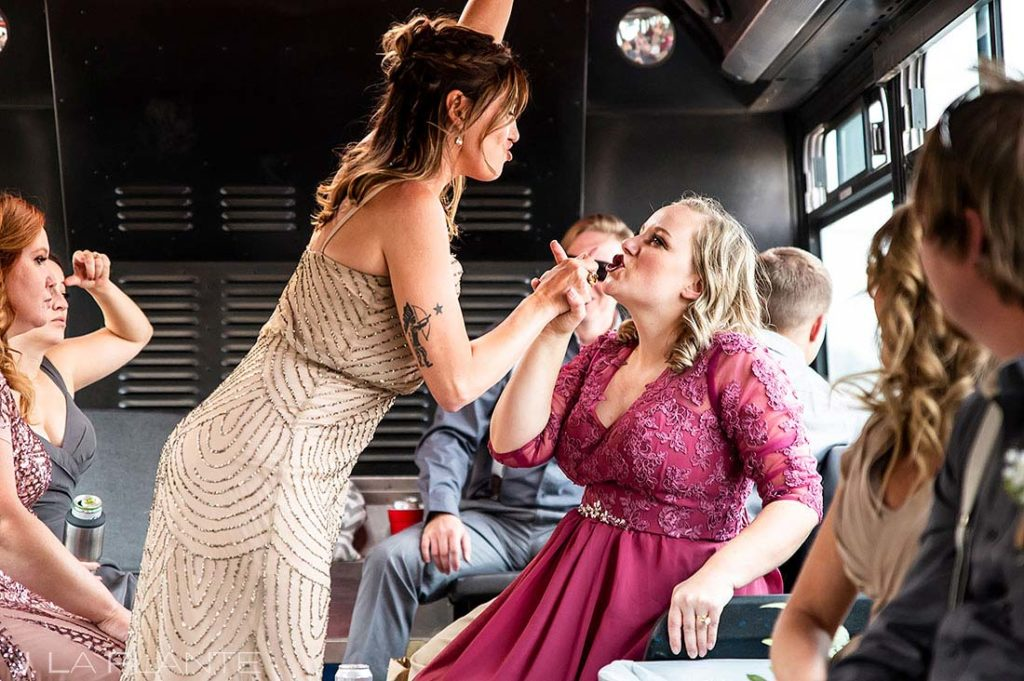 bridesmaids goofing around on the party bus