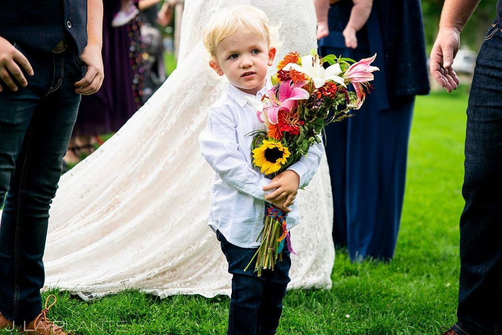 son of the bride holding the bride's bouquet