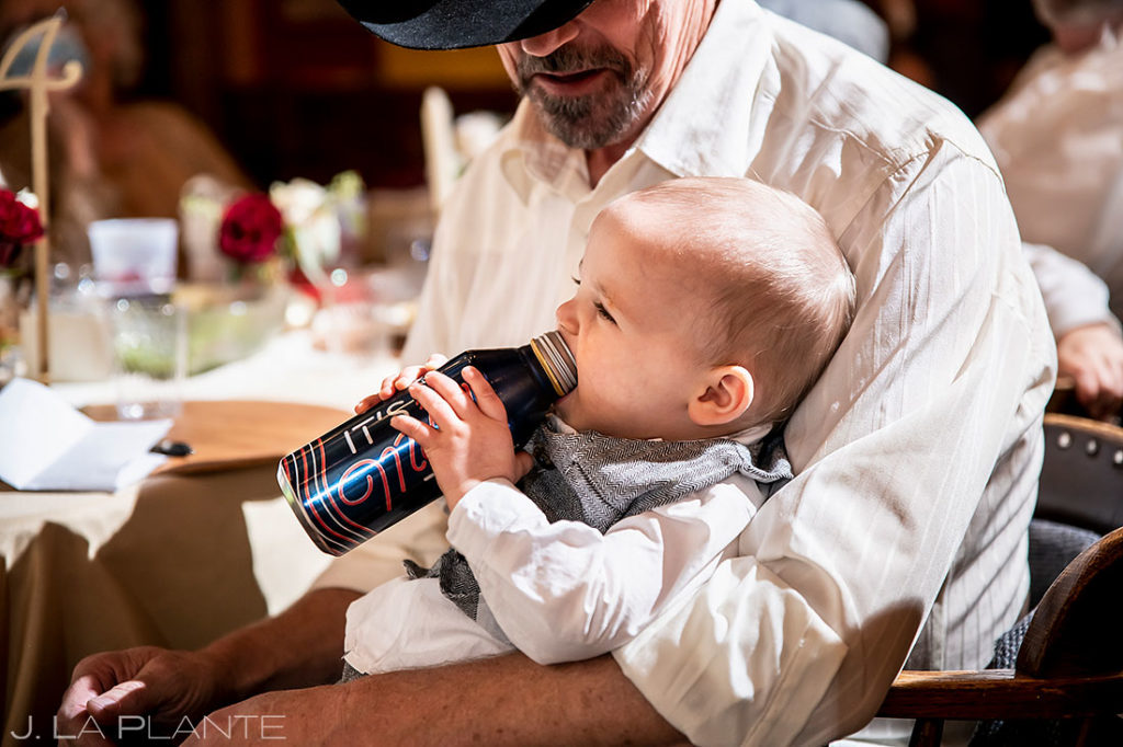 infant son of the bride and groom trying to drink beer bottle