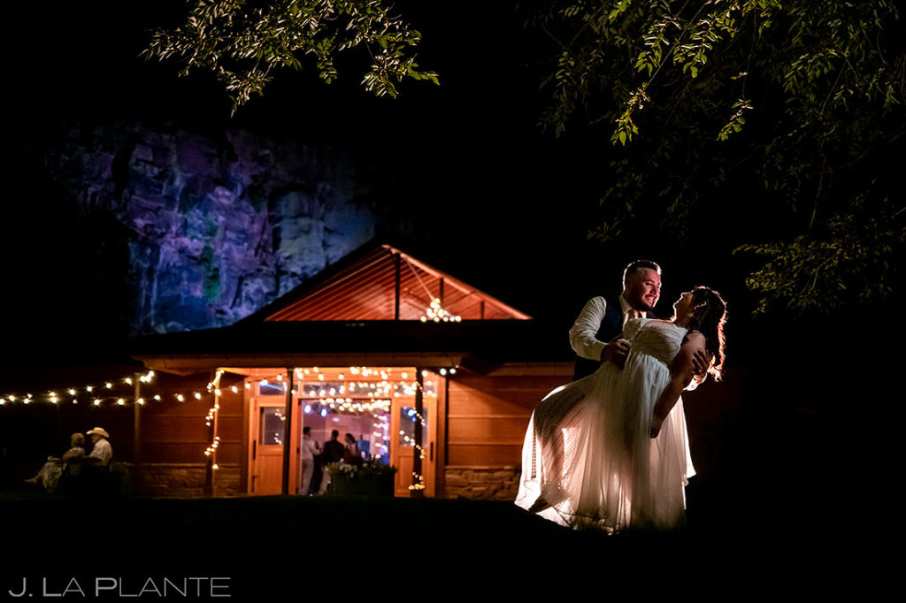 nighttime portrait of bride and groom outside wedding venue