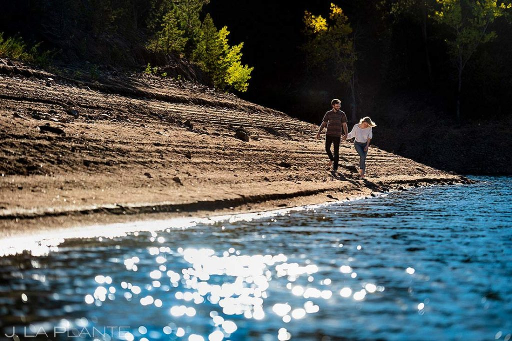 canoeing engagement session bride and groom walking on beach